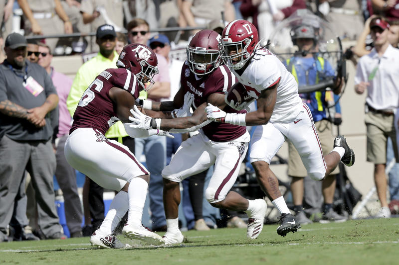 Alabama wide receiver Jaylen Waddle (17) breaks free from Texas A&M defenders to score on a 31-yard catch and run during the first quarter of an NCAA college football game, Saturday, Oct. 12, 2019, in College Station, Texas. (AP Photo/Sam Craft)