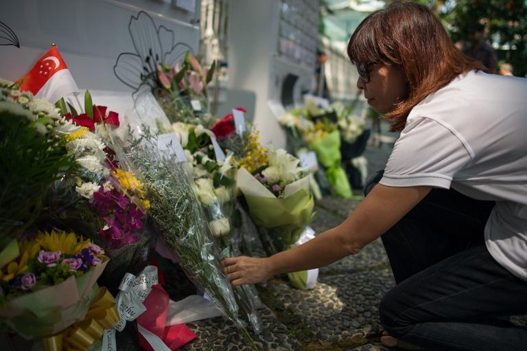 A Singaporean lays flower at the entrance to the Istana presidential palace following the death of former prime minister Lee Kuan Yew on March 23, 2015