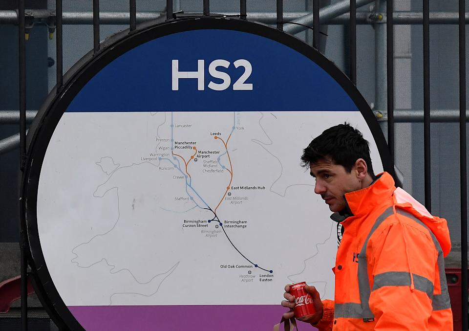 An HS2 worker walks past signage on perimeter fencing at the HS2 high speed rail link construction site in Euston, London, Britain, December 18, 2019. REUTERS/Toby Melville