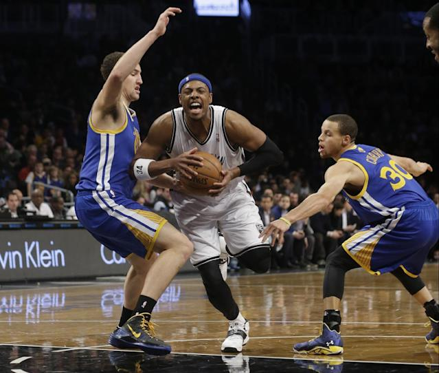Brooklyn Nets' Paul Pierce (34) drives past Golden State Warriors' Stephen Curry (30) and Andrew Bogut (12), of Australia, during the first half of an NBA basketball game Wednesday, Jan. 8, 2014, in New York. (AP Photo/Frank Franklin II)