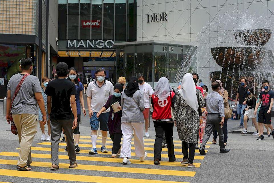 People wearing face masks crossing the road in front of Pavillion in Kuala Lumpur October 10, 2021. — Picture by Yusof Mat Isa