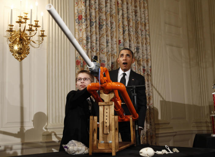 """Ready, aim, fire the sweet goo! The president appears to be having a wee bit too much fun as he watches one Joey Hudy of Phoenix, Ariz., launch a marshmallow from his """"Extreme Marshmallow Cannon"""" at the White House for the second White House Science Fair on Feb. 7, 2012. (Kevin Lamarque/Reuters)"""