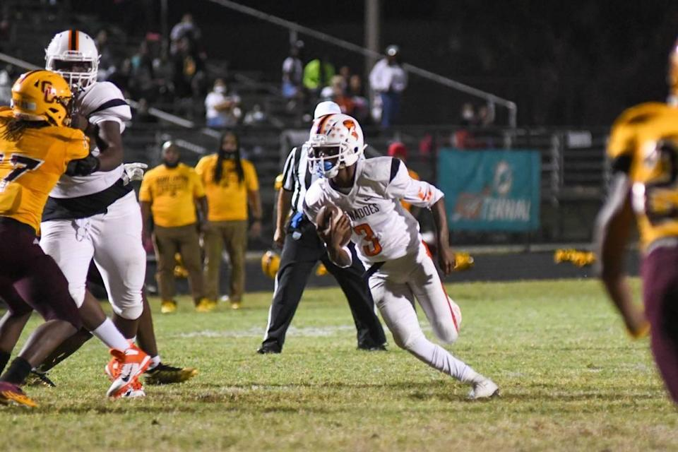 Booker T. Washington quarterback Torrey Morrison scrambles in the first half against Glades Central in a South Florida Tri-County tournament game on Friday, Dec. 4, 2020, in Belle Glade, Florida.