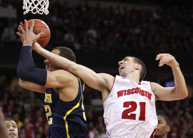 Wisconsin's Josh Gosser, right, reaches for the ball held by Michigan's Jordan Morgan during the first half of an NCAA college basketball game Saturday, Jan. 18, 2014, in Madison, Wis. (AP Photo/Andy Manis)