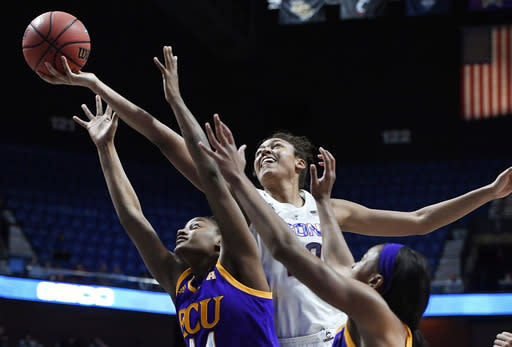 Connecticut's Olivia Nelson-Ododa reaches for a rebound over East Carolina's Destiny Campbell, left, and Raven Johnson, right, during the first half of an NCAA college basketball game in the American Athletic Conference tournament quarterfinals, Saturday, March 9, 2019, at Mohegan Sun Arena in Uncasville, Conn. (AP Photo/Jessica Hill)
