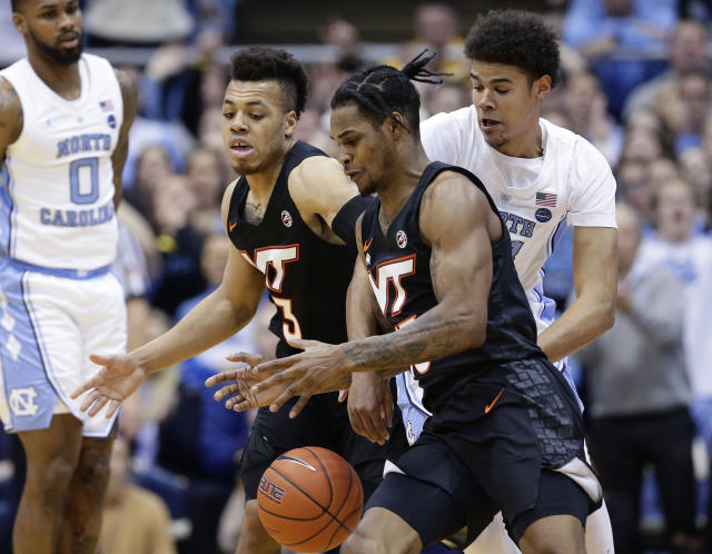 Virginia Tech's Wabissa Bede (3) and Ahmed Hill chase the ball with North Carolina's Cameron Johnson, right, during the first half of an NCAA college basketball game in Chapel Hill, N.C., Monday, Jan. 21, 2019. (AP Photo/Gerry Broome)