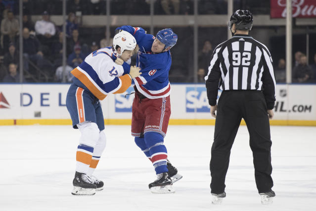 Linesman Mark Shewchyk (92) watches New York Islanders left wing Matt Martin (17) fight New York Rangers left wing Cody McLeod (8) during the first period of an NHL hockey game, Thursday, Jan. 10, 2019, at Madison Square Garden in New York. (AP Photo/Mary Altaffer)