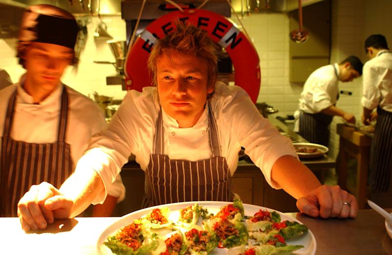 File photo dated 07/11/02 of chef Jamie Oliver in the kitchen during the launch of his restaurant 'Fifteen' in London's Old Street. Jamie Oliver's restaurant group, which includes Jamie's Italian, Barbecoa and Fifteen, has appointed administrators putting more than 1,300 jobs at risk.