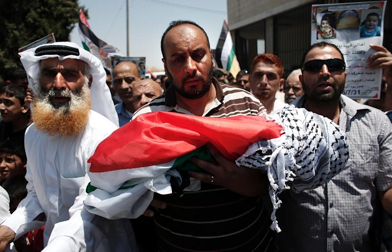 Relatives carry the body of 18-month-old Palestinian toddler Ali Saad Dawabsha, who died after his house was set on fire by Jewish settlers, during his funeral in the West Bank village of Duma on July 31, 2015 (AFP Photo/Thomas Coex)
