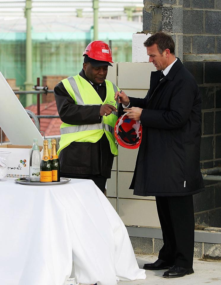 LONDON, ENGLAND - JANUARY 25:  Alec Stewart of Surrey Cricket Club signs an autograph as he talks to the waiter at the bar on the building site during the Topping Out of the new Vauxhall End Stand for Surrey County Cricket Club at The Brit Oval on January 25, 2005 in London, England. (Photo by Christopher Lee/Getty Images)