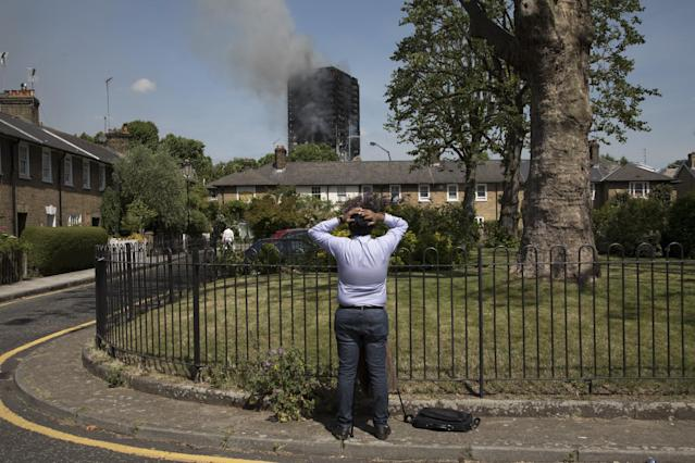<p>A person looks up at smoke rising as emergency fire services tackle the blaze at Grenfell Tower near Notting Hill on June 14, 2017 in West London, England (Photo: Mike Kemp/In Pictures via Getty Images) </p>