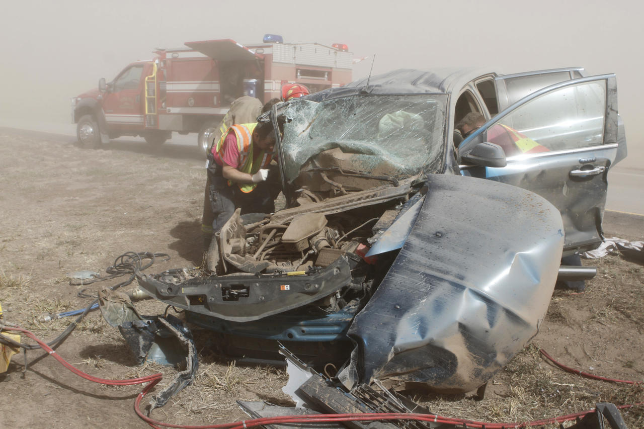 Rescue personnel work to extricate a woman pinned in vehicle after it was involved in a multi-vehicle accident on Interstate 35 on Thursday, Oct. 18, 2012, near Blackwell, Okla. Blackwell Police Chief Fred LeValley said nine people were injured, but there were no fatalities. (AP Photo/The Ponca City News, Rolf Clements)