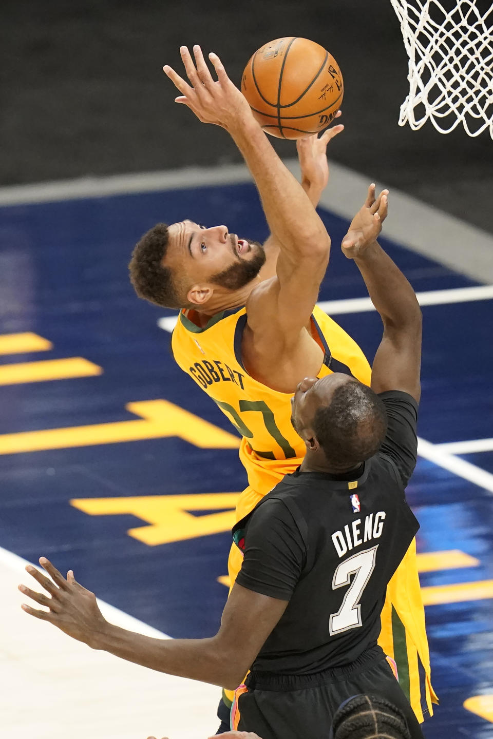 Utah Jazz center Rudy Gobert (27) and San Antonio Spurs center Gorgui Dieng (7) battle for a rebound in the first half during an NBA basketball game Monday, May 3, 2021, in Salt Lake City. (AP Photo/Rick Bowmer)