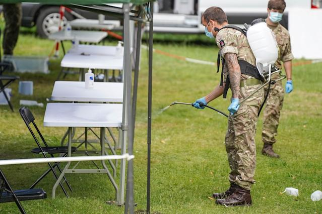 A member of the armed forces sprays disinfectant at a station set up for the testing for COVID-19 in Spinney Hill Park in Leicester. (Getty)