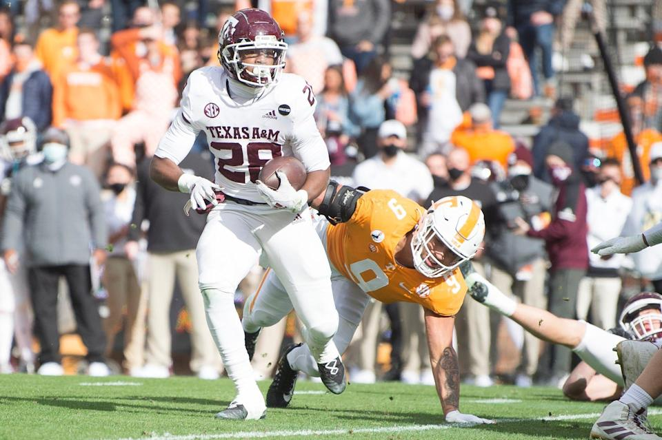 Texas A&M running back Isaiah Spiller runs the ball while defended by Tennessee linebacker Tyler Baron (9) during their game at Neyland Stadium in Knoxville, Tenn.