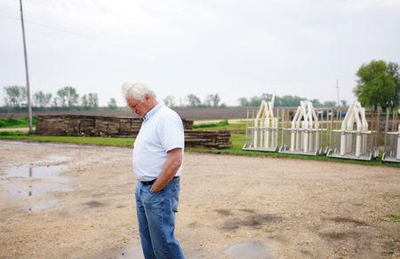 Farmer Ken Ries looks down at the ground outside his hog farm in Ryan, Iowa, U.S., May 18, 2019. Picture taken May 18, 2019.  REUTERS/Ben Brewer