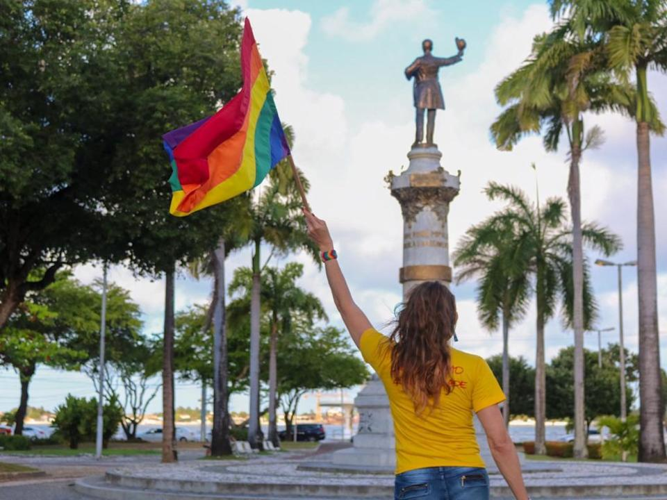 Linda Brasil waves an LGBT+ Pride flag with her back towards the camera in a yellow t-shirt
