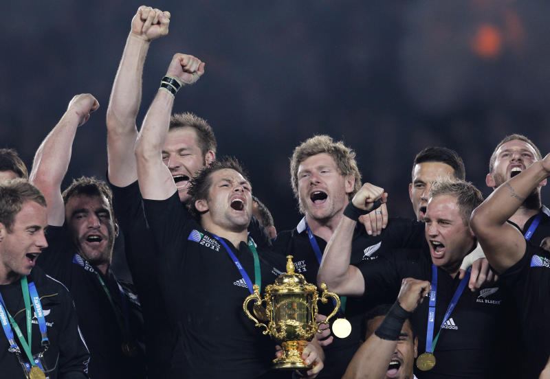 FILE - In this Oct. 23, 2011 file photo, New Zealand All Blacks captain Richie McCaw holds the Webb Ellis trophy as teammates celebrate after their Rugby World Cup final win over France in Auckland, New Zealand.  2011 was the year that the All Blacks stood up to the pressure of playing in their own backyard to clinch the Rugby World Cup for the first time since 1987, finally living up to their billing as the world's top rugby team, led by McCaw.(AP Photo/Christophe Ena, File)