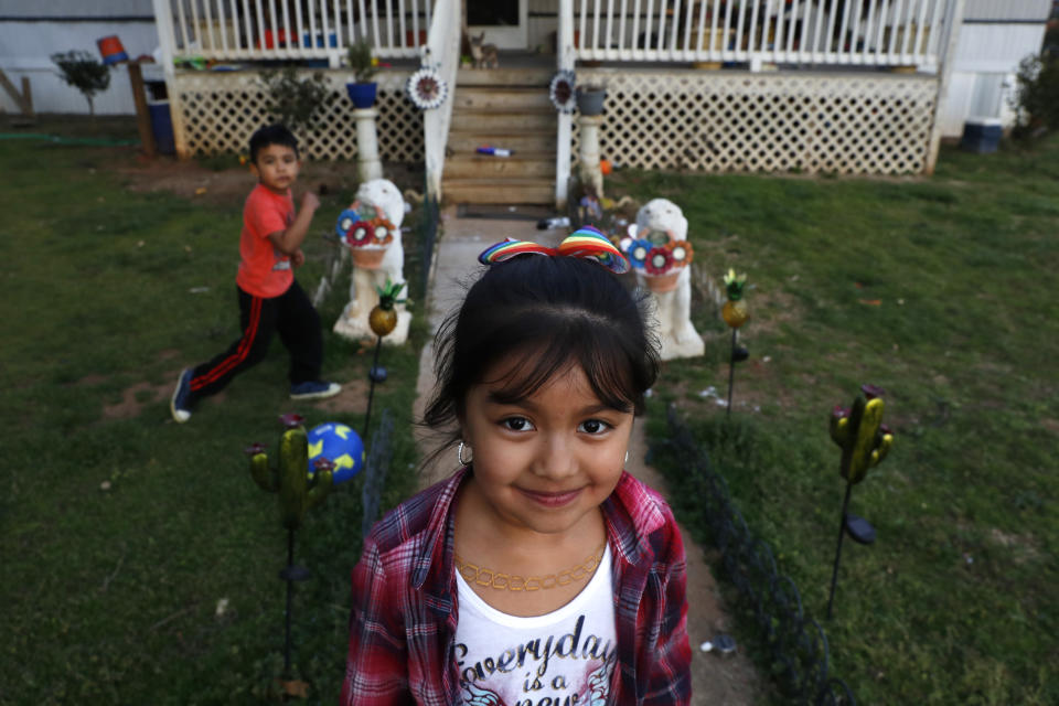 Dulce, 6, and her brother play in the yard of their family home across the railroad tracks in Burlington, N.C., Monday, March 9, 2020. (AP Photo/Jacquelyn Martin)