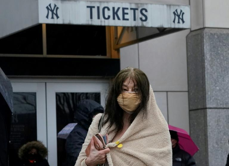 People line up in the rain outside the Yankee Stadium on February 5, 2021 in New York as the Stadium is turned into a mass Covid-19 vaccination site, which is strictly reserved for residents of The Bronx.