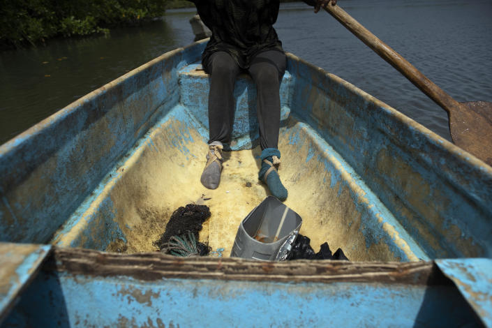 """Wearing socks to protect her feet when walking in the mangrove, Fatou Jatta, paddles in the estuary waters of the Gambia river in Serrekunda, Gambia, Saturday, Sept. 25, 2021. Afraid of the COVID-19 vaccine, Jatta, 66, says that """"some people will take it and will have more problems in their bodies"""". Their fears are hardly exceptional, with similar hesitancies and vaccine rumor proliferating across Africa. (AP Photo/Leo Correa)"""