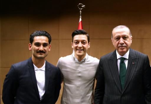 (ALTERNATIVE CROP) This handout picture taken on May 13, 2018 and released on May 14, 2018 by the Turkish Presidential Press office shows Turkish President Recep Tayyip Erdogan(R) posing for a photo with German footballers of Turkish origin Ilkay Gundogan (L) and Mesut Ozil (2nd L) in London