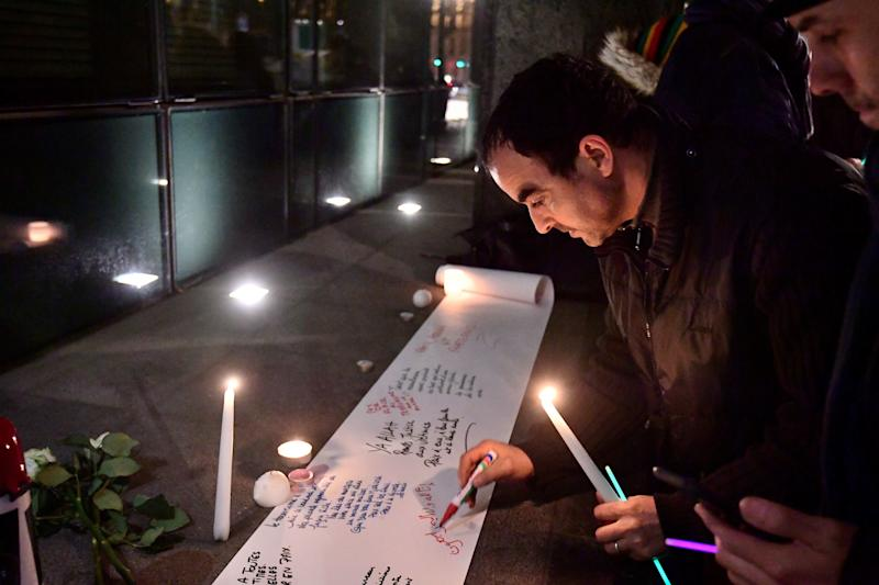 People write messages on a sheet of paper during a gathering at the New Zealander Embassy in Brussels to commemorate the victims of an attack on two mosques in New Zealand.