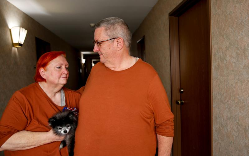 "Dennis and Denise Schlies pose for a portrait with their dog Guni, on Tuesday, Sept. 15, 2020 at a hotel in Salem, Oregon. Dennis Schlies is a 911 dispatcher known by many as the ""Voice of the Canyon."" Schlies was taking calls the night the wildfires exploded, all while his very own home in Gates, Oregon was burning down."