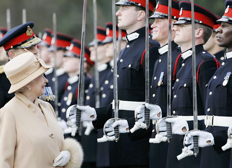 Queen Elizabeth II smiles at Prince Harry as she inspects soldiers at their passing-out Sovereign's Parade at Sandhurst Military Academy on April 12, 2006 in Surrey, England