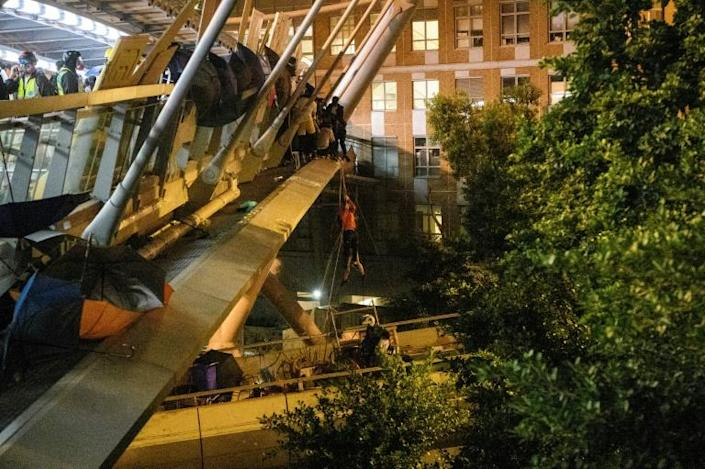 Dozens of people shinned down ropes from a footbridge in a bid to get away from the campus (AFP Photo/ANTHONY WALLACE)