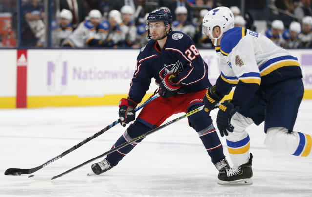 Columbus Blue Jackets' Oliver Bjorkstrand, left, of Denmark, carries the puck upice as St. Louis Blues' Carl Gunnarsson, of Sweden, defends during the second period of an NHL hockey game Friday, Nov. 15, 2019, in Columbus, Ohio. (AP Photo/Jay LaPrete)