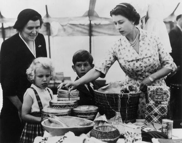 22nd August 1955: Queen Elizabeth II with Princess Anne, Prince Charles and their nurse, Helen Lightbody, at a stall during a Sale of Work event in Abergeldie Castle, near Balmoral Castle in Aberdeenshire. They are raising funds for the building of a new vestry at Craithie Church. (Photo by Fox Photos/Getty Images)