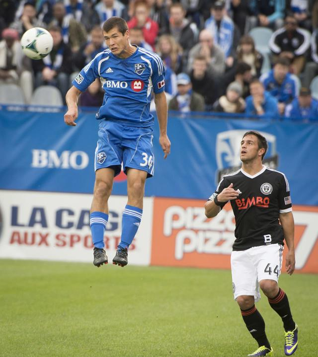 Montreal Impact's Karl W. Ouimette, left, heads the ball as Philadelphia Union's Daniel Cruz defends during the first half a MLS soccer game in Montreal Saturday, Oct. 19, 2013. (AP Photo/The Canadian Press, Peter McCabe)