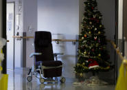 An empty chair is left in a hallway next to a Christmas tree in the COVID-19 ward at the St. Michiel Hospital in Brussels, Tuesday, Nov. 24, 2020. Nations are struggling to reconcile cold medical advice with a holiday tradition that calls for big gatherings in often poorly ventilated rooms, where people chat, shout and sing together, providing an ideal conduit for a virus that has killed over 350,000 people in Europe so far. (AP Photo/Virginia Mayo)