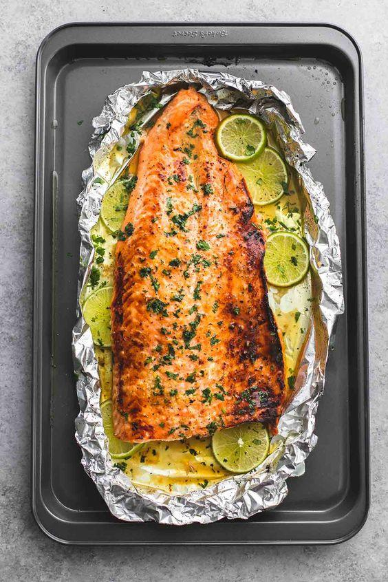 Baked honey cilantro lime salmon in foil is cooked to tender, flaky perfection in just 30 minutes with a flavorful garlic and honey lime glaze. | lecremedelacrumb.com: