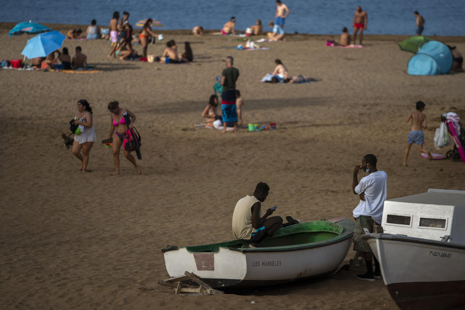 Two migrants sit on a fishing boat as people enjoy the beach in Gran Canaria island, Spain, on Friday, Aug. 21, 2020. Though migrant arrivals to mainland Spain via the Mediterranean Sea have decreased by 50% compared to last year, landings in the Canary Islands have increased by 550% and haven't been this high in over a decade, raising alarms at the highest levels of the Spanish government. (AP Photo/Emilio Morenatti)