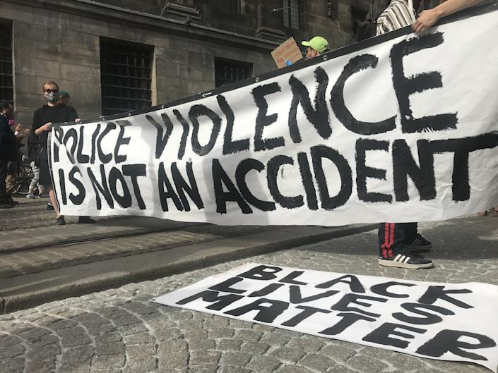 """<i>People shout slogans during a June 1 protest at Dam Square in Amsterdam over the death of George Floyd. The banner reads: """"Police violence is not an accident."""" </i>"""