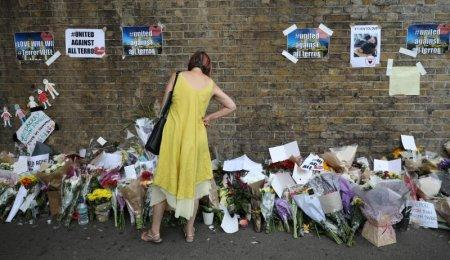 FILE PHOTO: A woman looks at messages at the base of a wall near the scene of an attack next to Finsbury Park Mosque, in north London, Britain June 20, 2017. REUTERS/Marko Djurica