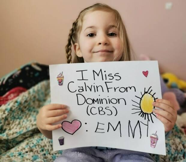 Emmy Laine, 4, holds a sign she made for Calvin Young, who works at the Dominion grocery store in Conception Bay South.