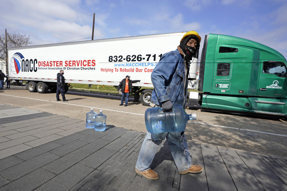James White carries a jug of donated water from a distribution site, Thursday, Feb. 18, 2021, in Houston. Houston and several surrounding cities are under a boil water notice as many residents are still without running water in their homes. (AP Photo/David J. Phillip)