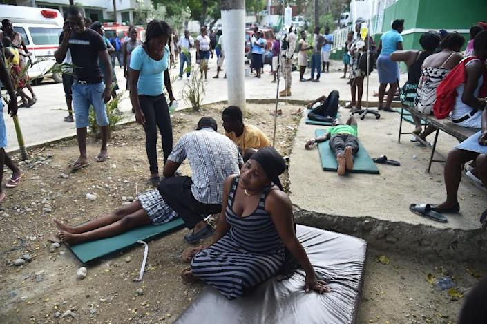 People are treated in the yard of the Immaculate Conception Hospital in the city of Port-de-Paix, October 7, 2018 following the earthquake. A 5.9-magnitude earthquake struck off the northwest coast of Haiti late Saturday, killing at least 12 people, injuring more than 130 others and damaging homes in the poverty-stricken Caribbean nation, authorities said. (AFP Photo/HECTOR RETAMAL)