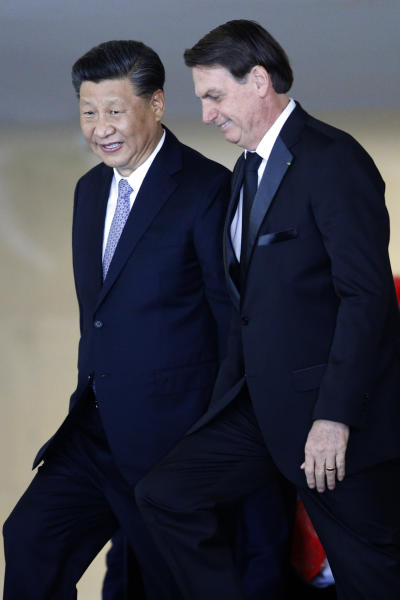 China's President Xi Jinping, left, walks with the Brazil's President Jair Bolsonaro, upon Xi Jinping's arrival for a bilateral meeting on the sidelines of the 11th edition of the BRICS Summit, at the Itamaraty Palace, in Brasília, Brazil, Wednesday, Nov. 13, 2019. (AP Photo/Eraldo Peres)