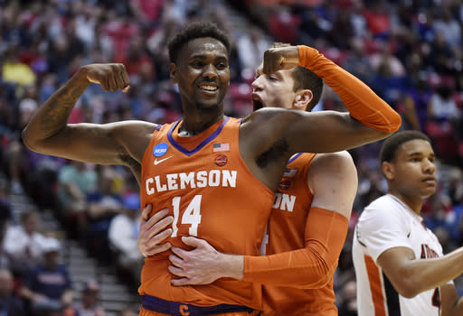 Clemson forward Elijah Thomas, front, celebrates a basket with forward David Skara during the first half of a second-round NCAA men's college basketball tournament game against Auburn on Sunday, March 18, 2018, in San Diego. (AP Photo/Denis Poroy)