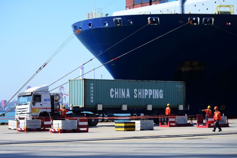 Truck transports a container next to a cargo vessel at a port in Qingdao, Shandong