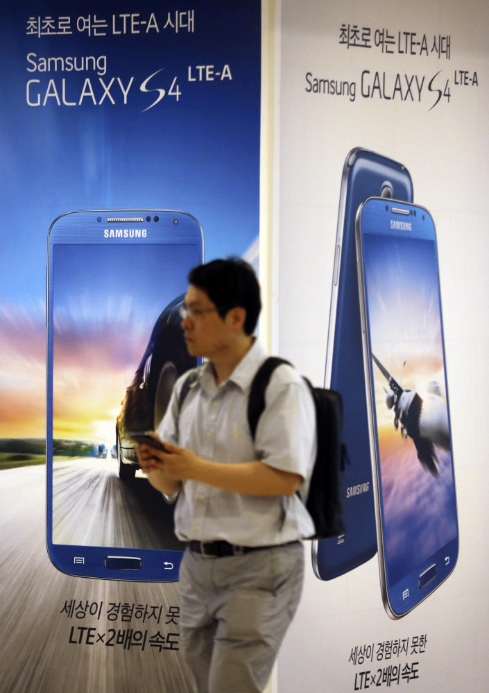 A man walks by the billboards of Samsung Electronics' Galaxy S4 LTE-A smartphone at a showroom of its headquarters in Seoul, South Korea, Friday, July 5, 2013. Even after setting a record high profit, Samsung Electronics disappointed investors who increasingly doubt its mainstay smartphone business can maintain rapid growth. Samsung Electronics Co. on Friday estimated its April-June operating profit at a record high of 9.5 trillion won ($8.3 billion). But it fell short of forecasts by analysts who held higher expectation for the world's largest smartphone maker. (AP Photo/Lee Jin-man)