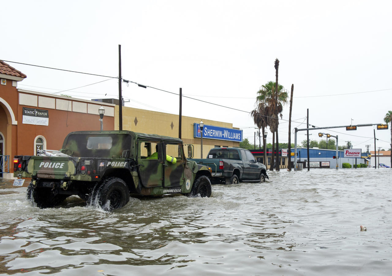 A military all-terrain vehicle pushes into floodwaters Wednesday, June 20, 2018, on Texas Avenue in Weslaco, Texas. Heavy rains along the Texas coast have caused flooding in areas that were hit hard by Hurricane Harvey less than a year ago. (Jason Hoekema/The Brownsville Herald via AP)