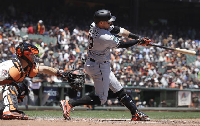 Miami Marlins' Miguel Rojas, right, hits an RBI-single in front of San Francisco Giants catcher Nick Hundley during the second inning of a baseball game in San Francisco, Wednesday, June 20, 2018. (AP Photo/Jeff Chiu)