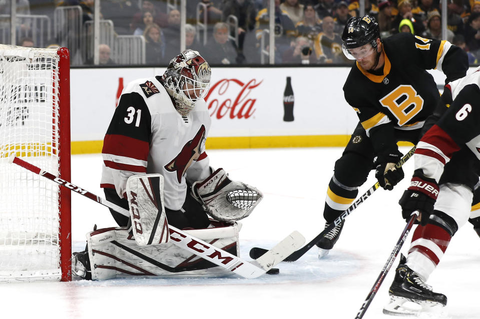 Arizona Coyotes goaltender Adin Hill makes a save as Boston Bruins' Chris Wagner looks for the rebound during the third period of an NHL hockey game Saturday, Feb. 8, 2020, in Boston. (AP Photo/Winslow Townson)