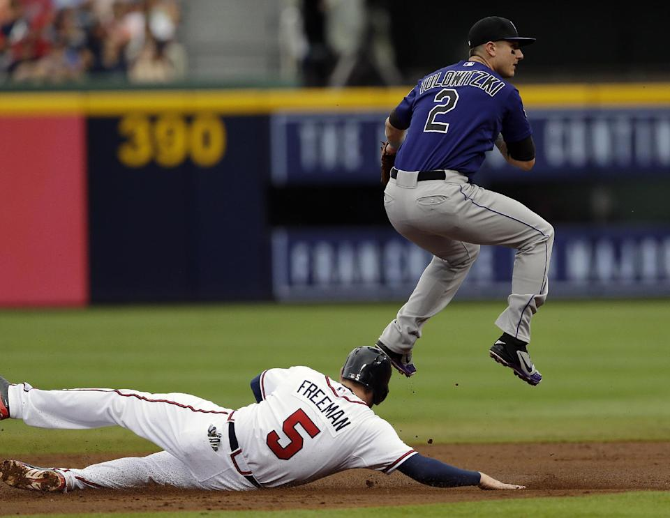 Colorado Rockies shortstop Troy Tulowitzki (2) avoids Atlanta Braves' Freddie Freeman (5) while turning a double play on a Brian McCann ground ball in the first inning of a baseball game in Atlanta, Wednesday, July 31, 2013. (AP Photo/John Bazemore)