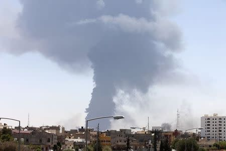 Smoke rises after rockets fired by one of Libya's militias struck and ignited a tank in Tripoli